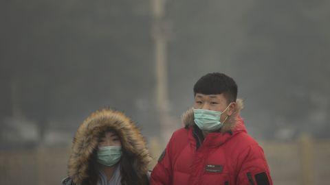 People wearing face masks walk across Tiananmen Square in Beijing on November 28.