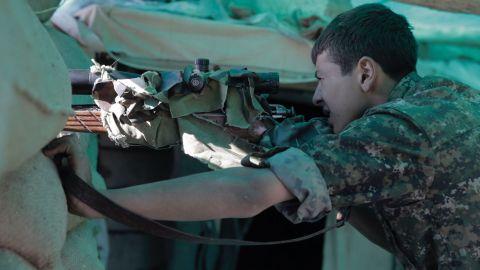 A Kurdish sniper takes position, his gun camouflaged.