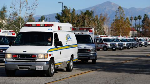 Ambulances pull out of a staging area near the Inland Regional Center.
