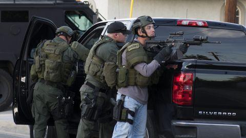 Law enforcement officers search a neighborhood in San Bernardino.