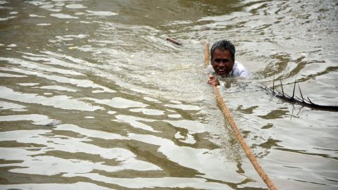 An Indian man clings to a rope as he makes his way through flood waters in Chennai on December 2,aid.