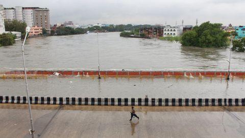 A man runs through a bridge across an over-flowing Adyar River in Chennai, Tamil Nadu, India, Wednesday, December 2, 2015.