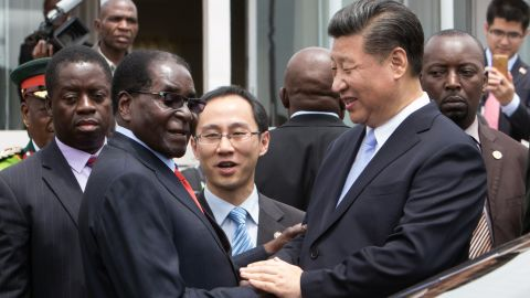 China's President Xi Jinping (2nd R) shakes  hands  with Zimbabwe's President Robert Mugabe (2nd L) as he arrive on December 1, 2015 in Harare.  China's President Xi Jinping visited Zimbabwe on December 1 on a rare trip by a world leader to a country shunned by Western powers over President Robert Mugabe's widely-criticised record on human rights.. The two leaders held talks and oversaw the signing by their ministers of 10 agreements and memorandums of understanding covering energy, aviation, telecommunications and investment promotion deals to shore up Zimbabwe's economy, which has fallen into dire straits under Mugabe's rule.