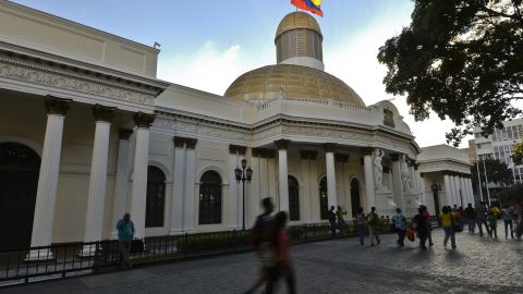 People walk past the National Assembly building in Caracas, on December 7, 2015. LUIS ROBAYO/AFP/Getty Images