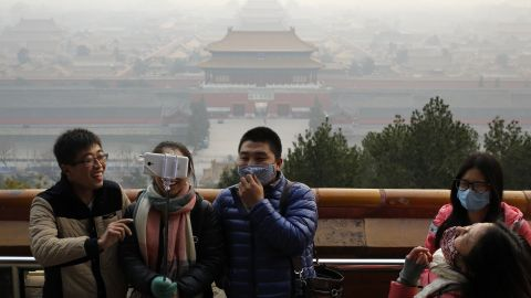 Visitors, some wearing masks to protect themselves from pollutants, share a light moment as they take a selfie at the Jingshan Park on a polluted day in Beijing on December 7, 2015, the day Beijing's city government issued its first red alert for pollution, the highest level of warning.