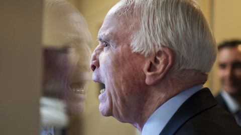 U.S. Sen. John McCain fools around with colleagues upon arriving at a news conference in Washington on Tuesday, January 13.