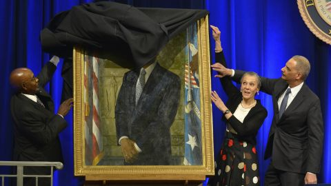 """A drape gets momentarily stuck as U.S. Attorney General Eric Holder and his wife, Sharon, help artist Simmie Knox unveil Holder's portrait at the Justice Department on Friday, February 27. Holder <a href=""""http://www.cnn.com/2015/04/24/politics/eric-holder-goodbye-ceremony/"""" target=""""_blank"""">resigned in April</a> and was replaced by Loretta Lynch."""