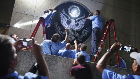 U.S. Embassy employees in Havana, Cuba, hang the seal of the United States a few hours before its ceremonial flag-raising on Friday, August 14. Cuba and the United States re-established diplomatic relations in July.