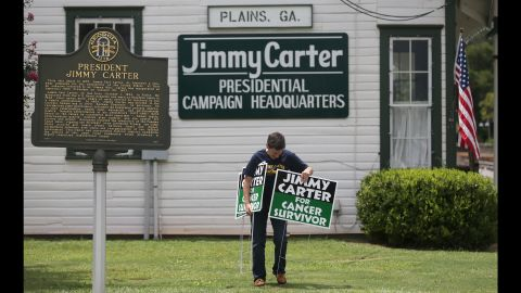 """Jill Stuckey places signs in front of Jimmy Carter's former campaign headquarters in Plains, Georgia, on Thursday, August 20. During a news conference in Atlanta that day, the former U.S. President <a href=""""http://www.cnn.com/2015/08/20/politics/jimmy-carter-cancer-update/index.html"""" target=""""_blank"""">announced that he had cancer spots on his brain</a> and would immediately begin a regimen of treatment. Carter <a href=""""http://www.cnn.com/2015/12/08/health/jimmy-carter-cancer-legacy/index.html"""" target=""""_blank"""">announced in December</a> that he was cancer-free."""