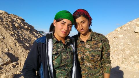 """Two members of the YPK, the Kurdish """"Women's Defence Units,"""" on the front lines south of Al-Houl, in Al-Hassakeh province."""