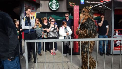 Bystanders watch as a person dressed in a Chewbacca costume walks near where fans have been congregating at the plaza in front of the TCL Theatre.