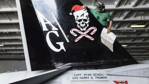 """Aviation Structural Mechanic Airman V. Sek, assigned to the """"Jolly Rogers"""" of Strike Fighter Squadron (VFA) 103, applies a Christmas decal to an F/A-18F Super Hornet in the hangar bay of the Nimitz-class aircraft carrier USS Harry S. Truman in December 2015."""