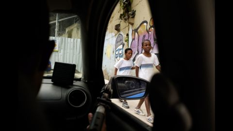 """Two children walk past a police checkpoint in Rio de Janeiro. While visiting the city's infamous favelas, photographer Matteo Bastianelli explored the complex relationship between some of Rio's poorest residents and the state's security forces. He's titled his project """"Suppressed Favelas."""""""