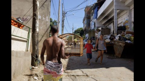 A man carries a birdcage through the streets of Cantagalo.