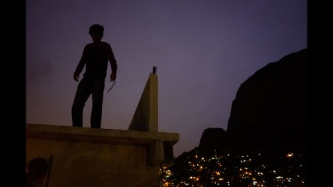 A man stands on the roof of the building where he works in Rocinha, the largest favela in Brazil.