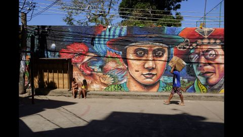 A man carries a package while two young women sit in front of a mural in Rio.