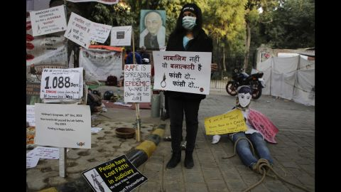 """An Indian woman holds a placard which reads, """"He is not a juvenile but a rapist, hang him"""" on Wednesday, December 16, during a demonstration to commemorate the third anniversary of the fatal 2012 rape."""