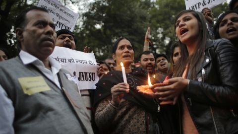 The parents, left and center, of the Indian student victim who was gang raped three years ago join others at a candlelit vigil in New Delhi on December 16.