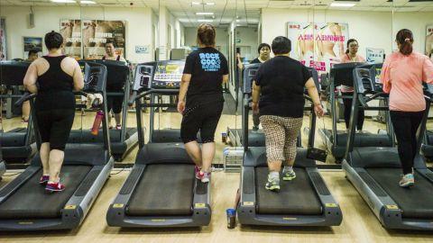 People walk on treadmills in a gymnasium.