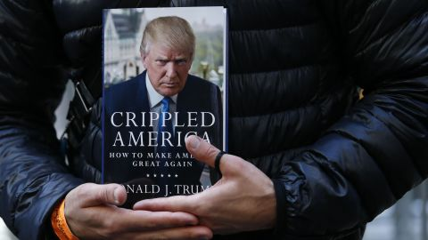 """A man holds a copy of Trump's newest book, """"Crippled America: How to Make America Great Again,"""" while he waits to have it signed by Trump outside Trump Tower in New York on November 3."""