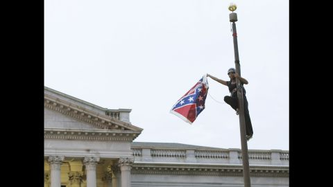 """A battle waged against the Confederate flag as a symbol of hatred after Dylann Roof was accused of killing nine people in a South Carolina church in an attempt to spark a race war. Activist Brittany """"Bree"""" Newsome took the battle flag off the flagpole at the Statehouse in Columbia, South Carolina."""