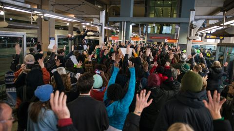 """MINNEAPOLIS, MN -  DECEMBER 23:  Black Lives Matter protestors hold their hands in the air and chant, """"Hands up, don't shoot,"""" at the Minneapolis-St. Paul International airport Lightrail stop on December 23, 2015 in Minneapolis, Minnesota. Black Lives Matter Minneapolis staged a brief protest at the Mall of America in Bloomington, MN before moving their protest to the airport. (Photo by Stephen Maturen/Getty Images)"""