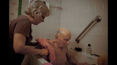 """Power comforts her father in the bathroom. Power is a nurse, and she came almost every day to help her father with whatever he needed. """"She was happy to bend over backward to continue to work and do all these things with her chin up,"""" Driscoll said. """"She knew her role and she did it with a certain pride. I thought it was really beautiful to be able to document that."""""""