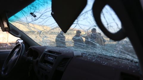 Afghan security personnel are seen through the shattered windshield of a damaged car after a suicide car bomb attack near the Kabul airport in Kabul, Afghanistan.