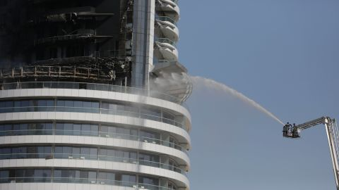 Firefighters spray water on a fire burning in the Address Downtown skyscraper in Dubai, United Arab Emirates on Friday, Jan. 1, 2016. The blaze began Thursday night before Dubai's annual New Year's Eve fireworks show at the Burj Khalifa, the world's tallest building which sits nearby. (AP Photo/Sunday Alamba)