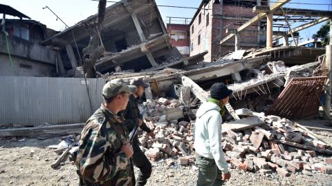 Security personel walk past a collapsed building following a 6.7 magnitude earthquake, in Imphal on December 4, 2015.  At least eight people were killed and scores injured January 4, when a strong 6.7 magnitude earthquake struck northeast India, sending panicked residents fleeing into the streets even hundreds of kilometres away in Bangladesh.   AFP PHOTO/ BIJU BORO / AFP / BIJU BORO        (Photo credit should read BIJU BORO/AFP/Getty Images)