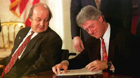 James Brady, the Reagan Administration press secretary who was wounded during the 1981 attempted assassination on Ronald Reagan, watches as Bill Clinton signs the Brady Bill at the White House on 30 November 1993.