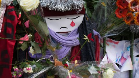 TOPSHOT - A doll crying is seen among flowers at a makeshift memorial in tribute to the victims of the Paris terror attacks, on January 4, 2016, outside the Bataclan concert hall in Paris, ahead of the one year anniversary of the jihadist attack on French satirical weekly newspaper Charlie Hebdo. Eight Charlie Hebdo staff were among the victims of the January 7, 2015 assault which brought millions of people onto France's streets in protest and transformed a fading publication into a global symbol of freedom of expression. / AFP / JOEL SAGET        (Photo credit should read JOEL SAGET/AFP/Getty Images)