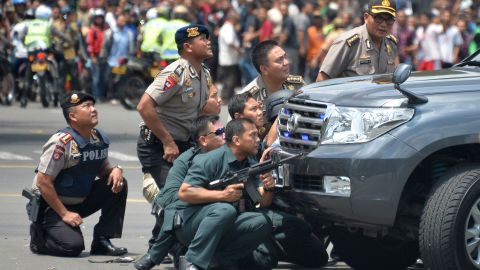 TOPSHOT - Indonesian police take position behind a vehicle as they pursue suspects after a series of blasts hit the Indonesia capital Jakarta on January 14, 2016. A series of bombs killed at least three people in the Indonesian capital Jakarta on January 14, with shots fired outside a cafe as police moved in, an AFP journalist at the scene said.     AFP PHOTO / Bay ISMOYO / AFP / BAY ISMOYO        (Photo credit should read BAY ISMOYO/AFP/Getty Images)