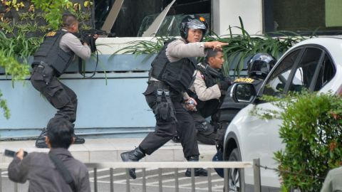 Indonesian police take position and aim their weapons as they pursue suspects outside a cafe after explosions went off in Jakarta on January 14.