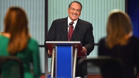 """Huckabee laughs during the debate, which was hosted by the Fox Business Network. His opening statement was much more serious. """"There are a lot of people who are hurting today,"""" said the former Arkansas governor. """"I wish the President knew more of them. He might make a change in the economy and the way he's managing it."""""""