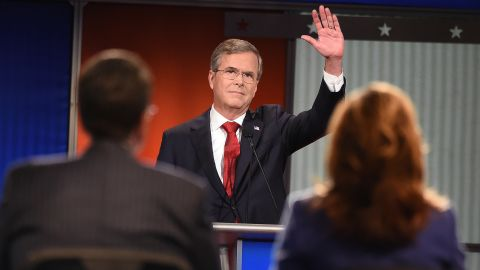 """Bush waves to the audience. The former Florida governor has been trying to build momentum that he had in the early stages of his candidacy, and he went after Democratic candidate Hillary Clinton early in the debate. """"She's under investigation with the FBI right now,"""" he said. """"If she gets elected, her first 100 days, instead of setting an agenda, she might be going back and forth between the White House and the courthouse. We need to stop that."""""""