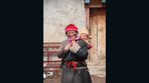 Woman with a child, Tibetan plateau, Qinghai province, China. Snow leopards inhabit a diverse realm -- monarchies, republics and communist states where many religions are practiced.