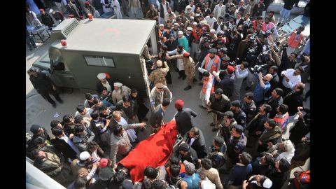 Rescue workers move an injured victim to an army ambulance from a hospital.