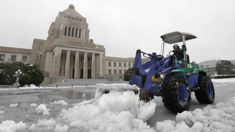 A man removes snow from the forecourt of the Diet building in Tokyo on January 18. Japanese transportation authorities said that over 60 flights were canceled due to heavy snow.