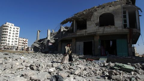 Yemenis walk past the site of a Saudi-led airstrike that targeted a building in Sanaa, Yemen, on January 25, 2016.