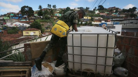 A Brazilian soldier inspects a home in Recife on Monday, January 25, while canvassing the neighborhood and attempting to eradicate the larvae of mosquitoes linked to the virus.