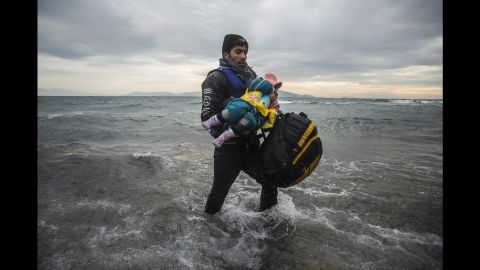 A man carries a child to the shore on January 3.