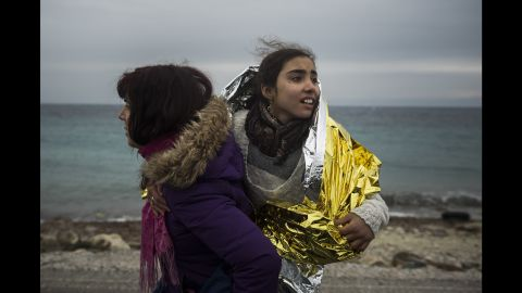 A volunteer walks along the seaside holding a child on January 3.
