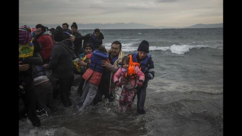 Refugees are helped as they reach the shore on January 3.
