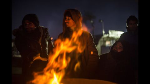 Men from Pakistan try to keep warm next to a makeshift fire outside a registration center in Moria on Friday, January 1.