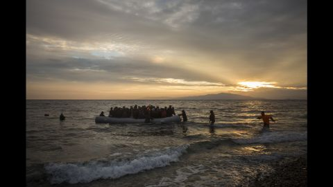 Volunteers rush to help refugees and migrants as they arrive on the shore of Lesbos on January 3.