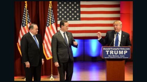 Donald Trump (R) speaks as Rick Santorm (C) as Mike Huckabee (L) look on during a Trump campaign rally raising funds for US military veterans at Drake University in Des Moines, Iowa on January 28, 2016.