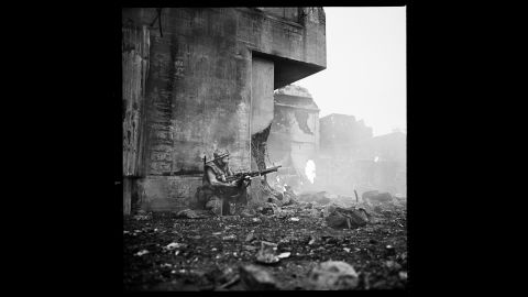 """Adam Baldwin as Animal Mother in a scene at Beckton Gas Works in November 1985. """"In this shot, Adam Baldwin is trying to locate the sniper while Doc Jay (John Stafford) and Eightball (Dorian Harewood) bleed to death,"""" Modine said. """"Notice the rolled-up rain cover on the lower right. This was placed as an 'eyeline' for Adam, so that Dorian and John didn't have to lie in the cold, bloody, poisoned earth of Beckton."""""""