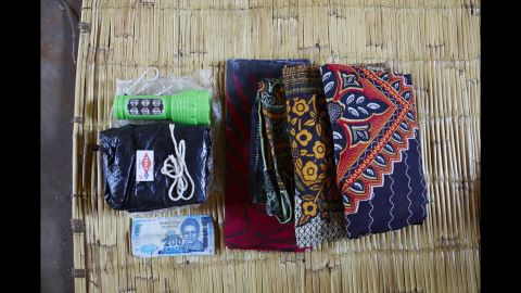 Ellen Phiri's bag includes: a flashlight because there is no electricity, a black plastic sheet to cover the delivery bed because it is it hard to clean the area, a razor blade to cut the umbilical cord, string to tie the umbilical cord, 200 Malawian Kwacha for food, three large sarongs for the mother to wear and to wrap her baby in.
