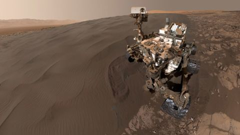 """NASA's Curiosity Mars rover took this selfie while sitting at """"Namib Dune."""" The rover is has been scooping up sand from the dune to analyze. The photo combines 57 images taken on January 19, 2016 during the rover's 1,228th Martian day, or sol. The photos were taken with the Mars Hand Lens Imager at the end of the rover's robotic arm."""